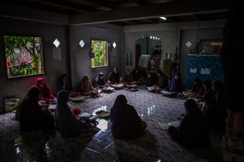 A women's group during their daily study of the Kitab, an Islamic holy book, at a community center in Ku Ching Lue Pah village, Narathiwat province, Thailand on November 15, 2017. Villagers here are frequently caught in the crossfire between Thai Army Rangers and insurgent groups, with many being killed or indefinitely detained under suspicion of aiding the nationalist rebels.